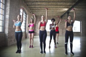 6 beautiful girls wearing yoga pants practicing group exercises