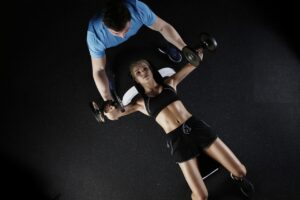 A woman training in the gym with the guidance of a Personal trainer