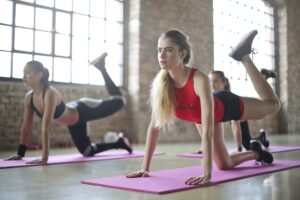 3 girls with red and black sport clothes doing yoga