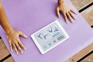 A woman getting ready to do Yoga, using mobile exercie app