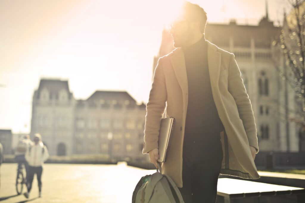 A guy with gray coat and laptop in his right hand walking on the street with the sun behind him, strugleing to find time to workout